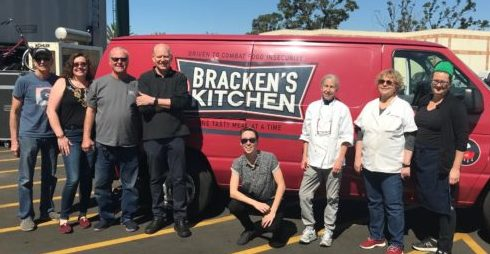 Volunteers from Bracken's Kitchen, OFRF staff, and volunteer chefs in front of Bracken's Kitchen van filled with donated food from luncheon