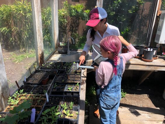 brise and her daughter watering seedlings in the greenhouse